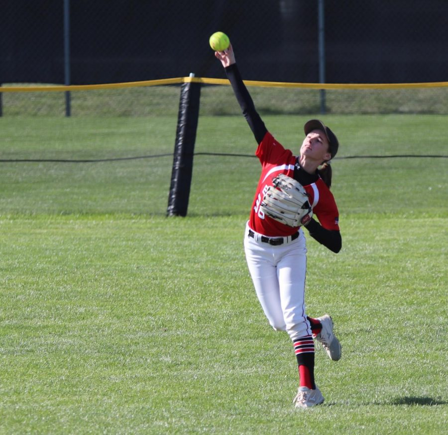 Kenzie Heedum reaches to throw a ball. She threw it back to the bases from the outfield.