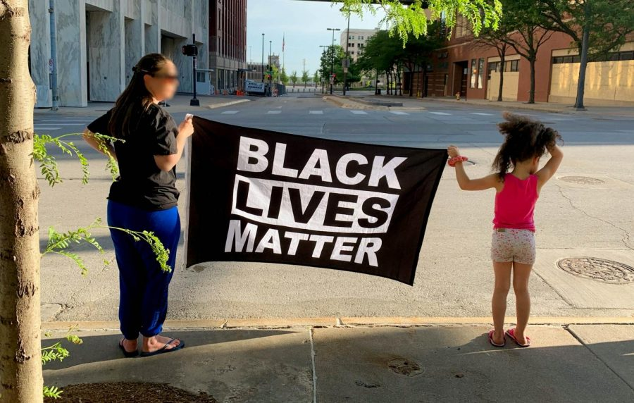 "A woman and a child hold up a  ""Black Lives Matter"" flag."