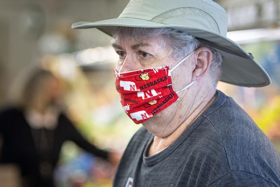 A man wears a Nebraska Huskers mask while in public.