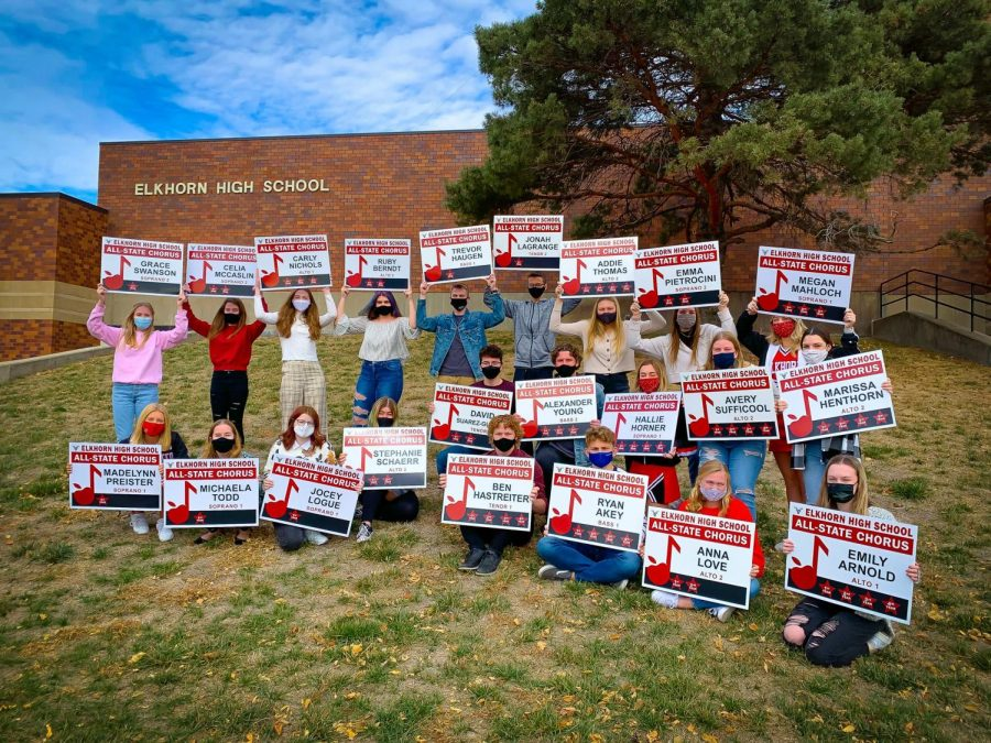 The group of students selected for All-State pose outside of the High School with their signs.