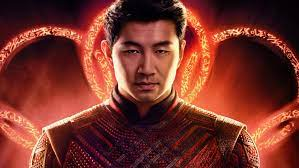 The main character Shang-Chi stands in front of images of the Ten Rings